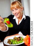 Lächelnde Frau bietet Salat auf Gabel zum Kosten an. Стоковое фото, фотограф Zoonar.com/Robert Kneschke / age Fotostock / Фотобанк Лори