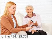 Frau misst den Blutzuckerspiegel mit Messgerät bei einer Seniorin... Стоковое фото, фотограф Zoonar.com/Robert Kneschke / age Fotostock / Фотобанк Лори
