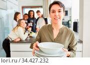 Junge Frau beim Teller tragen in WG Küche vor einer Gruppe Studenten. Стоковое фото, фотограф Zoonar.com/Robert Kneschke / age Fotostock / Фотобанк Лори