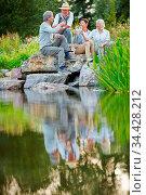 Zufriedene Senioren feiern mit einem Glas Wein im Garten am Teich. Стоковое фото, фотограф Zoonar.com/Robert Kneschke / age Fotostock / Фотобанк Лори