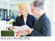 Zwei Geschäftsleute mit Akte reden im Büro miteinander über einen... Стоковое фото, фотограф Zoonar.com/Robert Kneschke / age Fotostock / Фотобанк Лори