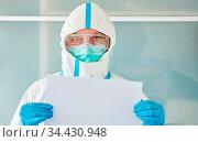 Mediziner in Schutzkleidung in Klinik hält Coronavirus Warnung in... Стоковое фото, фотограф Zoonar.com/Robert Kneschke / age Fotostock / Фотобанк Лори