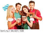 Vier glückliche Freunde beim Oktoberfest feiern in Dirndl und Lederhose... Стоковое фото, фотограф Zoonar.com/Robert Kneschke / age Fotostock / Фотобанк Лори