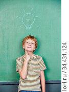 Kind vor Tafel mit Glühbirne beim Nachdenken in der Schule. Стоковое фото, фотограф Zoonar.com/Robert Kneschke / age Fotostock / Фотобанк Лори
