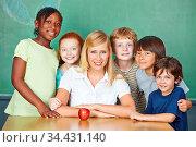 Lächelnde Lehrerin mit einer Gruppe ihrer Schüler in der Schule. Стоковое фото, фотограф Zoonar.com/Robert Kneschke / age Fotostock / Фотобанк Лори