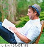 Mann liest ein Buch auf einem Stuhl im Garten im Sommer. Стоковое фото, фотограф Zoonar.com/Robert Kneschke / age Fotostock / Фотобанк Лори