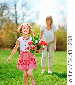 Mutter mit Tochter im Garten mit einem Strauß roter Tulpen. Стоковое фото, фотограф Zoonar.com/Robert Kneschke / age Fotostock / Фотобанк Лори
