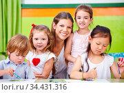 Lächelnder Erzieher und glückliche Kinder im Kindergarten malen. Стоковое фото, фотограф Zoonar.com/Robert Kneschke / age Fotostock / Фотобанк Лори