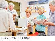 Senioren als freiwillige Helfer mit Kleiderspenden bei einer Spendensammlung. Стоковое фото, фотограф Zoonar.com/Robert Kneschke / age Fotostock / Фотобанк Лори