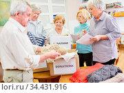 Gruppe Senioren sammelt Kleiderspende im Altersheim für Bedürftige. Стоковое фото, фотограф Zoonar.com/Robert Kneschke / age Fotostock / Фотобанк Лори