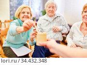 Senioren mit Demenz und Ärztin machen ein Spiel zusammen in der Gruppentherapie. Стоковое фото, фотограф Zoonar.com/Robert Kneschke / age Fotostock / Фотобанк Лори
