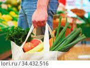 Mann trägt vollen Beutel mit Obst und Gemüse im Supermarkt. Стоковое фото, фотограф Zoonar.com/Robert Kneschke / age Fotostock / Фотобанк Лори