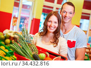 Lachendes Paar steht mit Korb voller Obst im Supermarkt. Стоковое фото, фотограф Zoonar.com/Robert Kneschke / age Fotostock / Фотобанк Лори