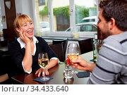 Lachende Frau im Gespräch mit Mann im Restaurant. Стоковое фото, фотограф Zoonar.com/Robert Kneschke / age Fotostock / Фотобанк Лори