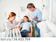 Kind auf einem Zahnarztstuhl wird von Zahnärztin behandelt. Стоковое фото, фотограф Zoonar.com/Robert Kneschke / age Fotostock / Фотобанк Лори