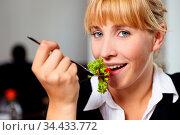 Lächelnde Frau mit grünem Salat auf Gabel im Restaurant. Стоковое фото, фотограф Zoonar.com/Robert Kneschke / age Fotostock / Фотобанк Лори