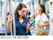 Girl using phone in underground carriage. Стоковое фото, фотограф Яков Филимонов / Фотобанк Лори