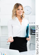Young girl with folder of documents is standing in modern office. Стоковое фото, фотограф Яков Филимонов / Фотобанк Лори