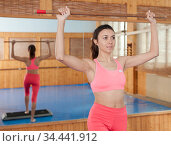 Woman doing exercise with gymnastic stick in fitness club. Стоковое фото, фотограф Яков Филимонов / Фотобанк Лори