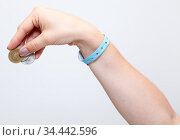 Female hand with blue hotel bracelet gives tip with coins money, grey background. Стоковое фото, фотограф Кекяляйнен Андрей / Фотобанк Лори