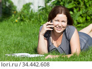 Smiling woman speaking with mobile phone while lying on green meadow in summer garden, book is on the grass, copyspace. Стоковое фото, фотограф Кекяляйнен Андрей / Фотобанк Лори