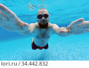 Middle aged man wear googles and swimming trunks submerged in water enjoy summer vacations swimming in pool. Active lifestyle and sport activity concept. Редакционное фото, фотограф Alexander Tihonovs / Фотобанк Лори