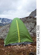 Green waterproof and windproof tent for hiking is in mountains at windy weather, standing behind big stone for protection from the wind. Стоковое фото, фотограф Кекяляйнен Андрей / Фотобанк Лори
