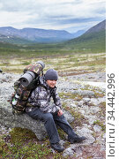 Adult mountaineer resting on stone with heavy backpack on his back, man hiking in mountain valley. Стоковое фото, фотограф Кекяляйнен Андрей / Фотобанк Лори