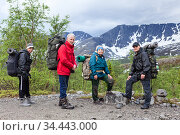 Caucasian family hiking together in mountains, mature grandparents with teenage and adult sons portrait against snowy mountain massif. Стоковое фото, фотограф Кекяляйнен Андрей / Фотобанк Лори