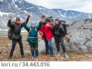 Mountaineers cheering and greeting with hands up, group of Caucasian hikers from one family hiking with backpacks in mountains. Стоковое фото, фотограф Кекяляйнен Андрей / Фотобанк Лори