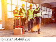 Industrie Arbeiter Gruppe in Halle einer Fabrik mit Paket auf Sackkarre. Стоковое фото, фотограф Zoonar.com/Robert Kneschke / age Fotostock / Фотобанк Лори