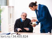 Police inspector arresting old judge in court. Стоковое фото, фотограф Elnur / Фотобанк Лори