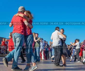 Happy adults are dancing tango or waltz on the city street
