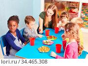 Kinder im Kindergarten essen Gemüse als Snack am Tisch mit Erzieherin. Стоковое фото, фотограф Zoonar.com/Robert Kneschke / age Fotostock / Фотобанк Лори