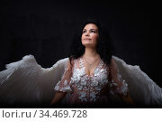 Girl with white wings posing in dark black studo during photoshoot with flour or dust and light. White angel in dark space. Стоковое фото, фотограф Кривошеина Елена Леонидовна / Фотобанк Лори