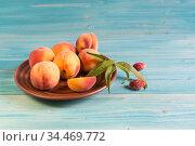 Свежие спелые персики на синем деревянном столе. Стоковое фото, фотограф Наталья Гармашева / Фотобанк Лори