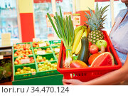 Frau hält einen mit Obst und Gemüse gefüllten Warenkorb in Supermarkt. Стоковое фото, фотограф Zoonar.com/Robert Kneschke / age Fotostock / Фотобанк Лори