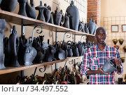 Portrait afro-ameciran man with ceramic tableware at shop. Стоковое фото, фотограф Яков Филимонов / Фотобанк Лори