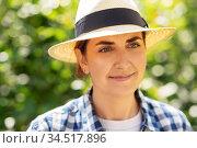 portrait of woman in straw hat at summer garden. Стоковое фото, фотограф Syda Productions / Фотобанк Лори