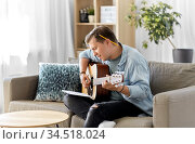 young man with music book playing guitar at home. Стоковое фото, фотограф Syda Productions / Фотобанк Лори