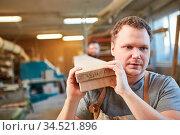 Arbeiter oder Schreiner Lehrling transportiert Holz Balken in der... Стоковое фото, фотограф Zoonar.com/Robert Kneschke / age Fotostock / Фотобанк Лори