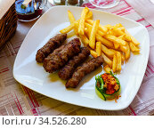 Cevapi - grilled dish of minced meat with french fries. Balkan cuisine. Стоковое фото, фотограф Яков Филимонов / Фотобанк Лори