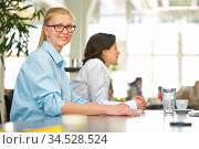 Geschäfsfrau sitzt bei einem Seminar im Konferenzraum am Tisch. Стоковое фото, фотограф Zoonar.com/Robert Kneschke / age Fotostock / Фотобанк Лори