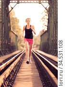 Active sporty woman running on railroad tracks bridge during morning... Стоковое фото, фотограф Zoonar.com/Matej Kastelic / easy Fotostock / Фотобанк Лори
