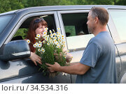 Мужчина и женщина возле машины с букетом ромашек. Стоковое фото, фотограф Марина Володько / Фотобанк Лори