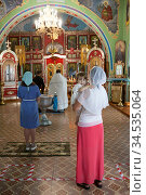 Godmother with kid wearing chrisom stand in the Orthodox church. Mother standing close to the baptistery. Ceremony of sacrament of initiation into the Christian church. Стоковое фото, фотограф Кекяляйнен Андрей / Фотобанк Лори