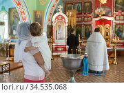 Godmother with goddaughter have ceremony of the Baptism of baby in the Orthodox church. People stand close to the baptistery. It is sacrament of initiation into the Christian church. Стоковое фото, фотограф Кекяляйнен Андрей / Фотобанк Лори