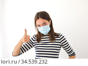Caucasian young woman with face mask showing thumb up. Стоковое фото, фотограф Ekaterina Demidova / Фотобанк Лори