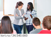 Lehrer im Unterricht mit einem Schüler vor der Klasse. Стоковое фото, фотограф Zoonar.com/Robert Kneschke / age Fotostock / Фотобанк Лори