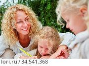 Zwei Kinder malen und zeichnen im Kindergarten neben einer Frau. Стоковое фото, фотограф Zoonar.com/Robert Kneschke / age Fotostock / Фотобанк Лори